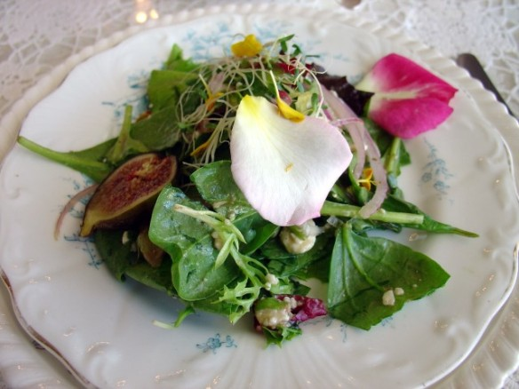 Fresh fig salad with greens and edible flowers