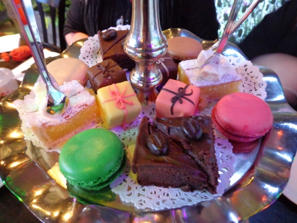 Assorted French macarons, petit fours, brownie triangles, and lemon squares with clotted cream